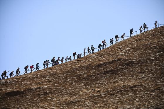 영구 출입 금지를 하루 앞둔 25일(현지시간) 관광객들이 줄지어 울룰루 암벽을 오르고 있다. [EPA=연합뉴스]