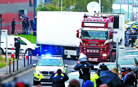 23일 영국 잉글랜드 남동부 에식스주에서 발견된 39구의 시신이 담긴 컨테이너를 경찰이 옮기고 있다. [AP=연합뉴스]
