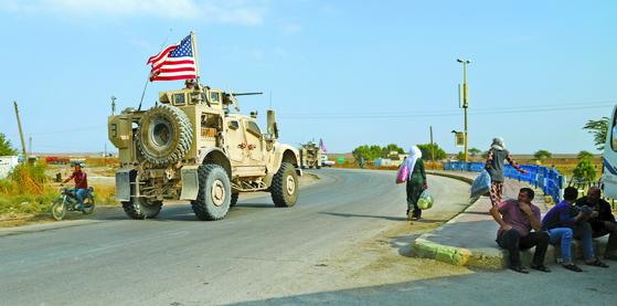 지난 20일 시리아 북부 쿠르드족 거점 지역에 주둔했던 미군 차량들이 이라크로 철군하고 있다. 철군에 분노한 일부 쿠르드 주민들은 미군 차량에 쓰레기와 돌멩이를 던지기도 했다. [EPA=연합뉴스]