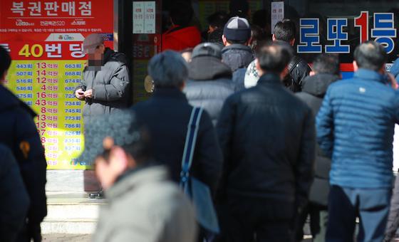 설 연휴 다음날인 지난 2월 7일 서울 노원구 로또 명당으로 알려진 복권판매점 앞에 시민들이 복권 구입을 위해 줄지어 서서 차례를 기다리고 있다. [연합뉴스]