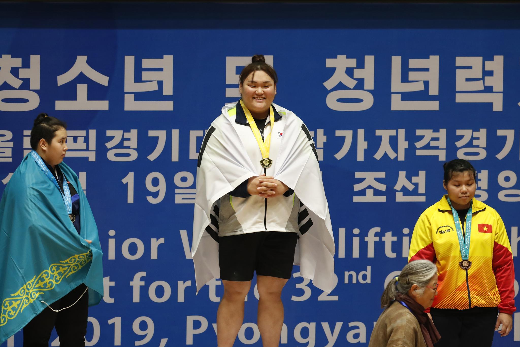 27일 오전 평양 청춘가역도전용경기장에서 열린 2019 아시아 유소년·주니어 역도선수권 대회 주니어 여자 87㎏급에 출전한 이선미가 시상식에서 금메달을 목에 걸은 채 웃고 있다. 사진공동취재단