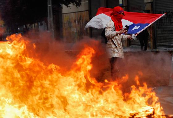 25일(현지시간) 칠레에서 국기를 든 한 집회참가자가 불타는 바리케이트 너머를 지나가고 있다. [로이터=연합뉴스]