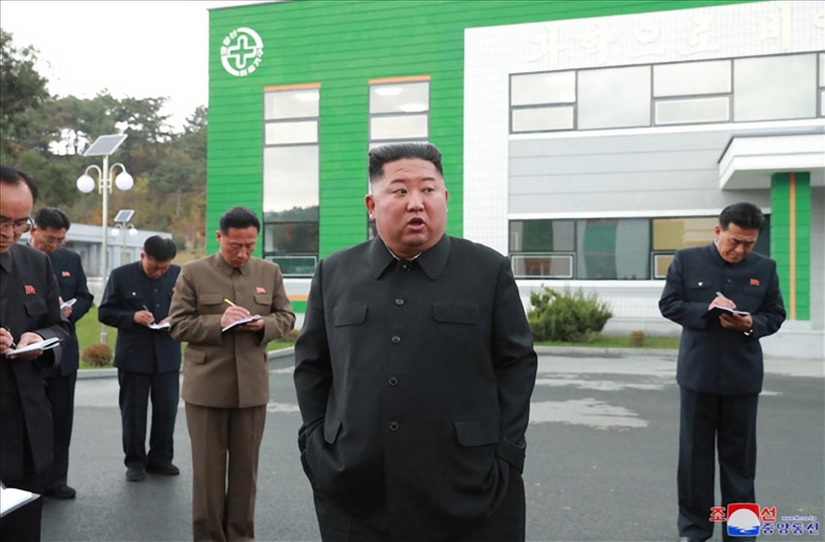 김정은 북한 국무위원장이 두 손을 주머니에 넣고 현지지도를 하고 있다. 당 간부들이 열심히 노트필기를 하고 있다. [조선중앙통신=연합뉴스]