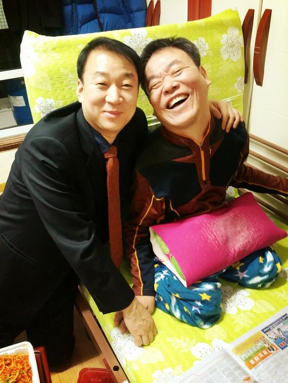 부산경찰청 이득찬(50) 행정관(왼쪽)이 20년째 후원하고 있는 뇌병변 장애인 신모(61)씨와 함께 활짝 웃고 있다. [사진 부산경찰청 이득찬 행정관]