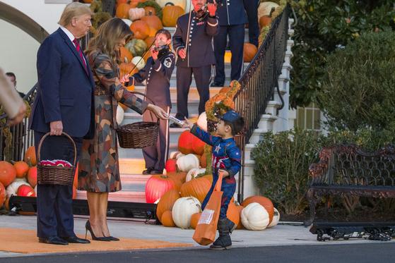 트럼프 대통령 부부가 28일 백악관 핼러윈데이 행사에서 한 어린이에게 사탕을 건네고 있다. [AP=연합뉴스]
