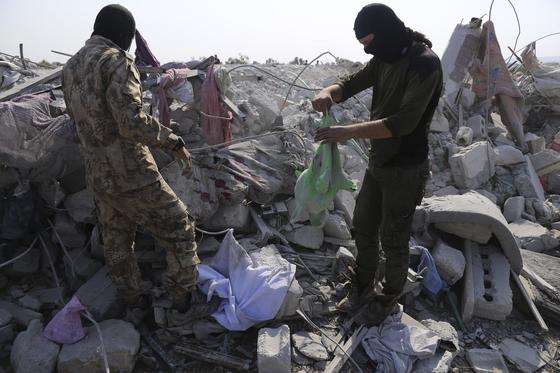 시리아 북서부 이들립 지역 주민들이 27일(현지시간) 아부 바크르 알바그다디가 숨어있던 은신처에서 잔해들을 수거하고 있다.[AP=연합뉴스]