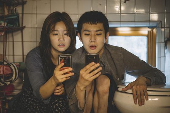 영화 '기생충' 주인공들이 화장실 변기 옆에 앉아 무료 와이파이를 찾고 있다. [사진 CJ엔터테인먼트]