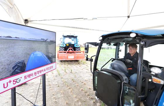 29일 경기 고양시 법곳동 농지에서 열린 LG유플러스 5G 스마트 농기계 시연회에서 농부가 트랙터를 원격조종하고 있다. [사진 LG유플러스]