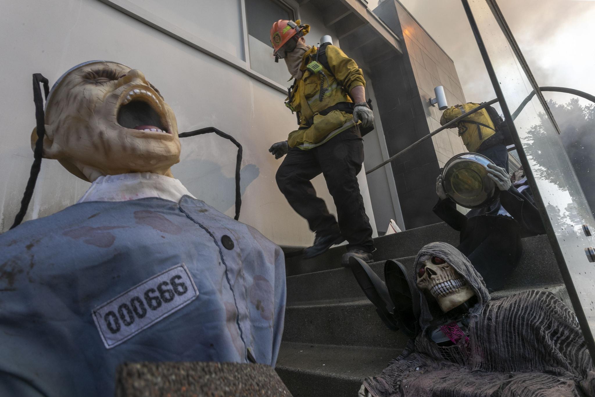 28일(현지시간) 캘리포니아 주 로스앤젤레스에서 발생한 화재로 불타버린 집에 좀비들이 쓰려져있다.[AFP=연합뉴스]