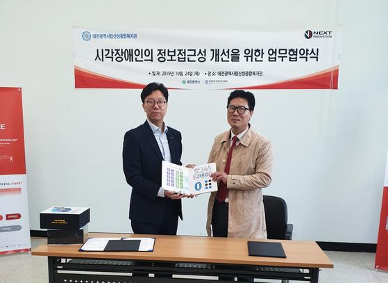 ㈜넥스트이노베이션 서인식대표와 (사)대전광역시립산성복지관 관장 이상용이 업무협약을 체결하고 있다.