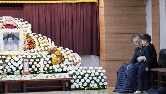 문재인 대통령이 30일 오전 부산 남천성당에 마련된 모친 고 강한옥 여사의 빈소에서 손주를 안고 대화를 나누고 있다. [사진 청와대]