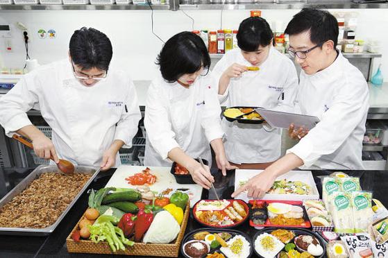 GS리테일은 편의점 GS25에서 판매하는 도시락·삼각김밥 등 먹거리의 질을 높이기 위해 노력 하고 있다. 식품연구소의 연구원이 상품 개발을 위해 테스트를 하고 있다. [사진 GS그룹]