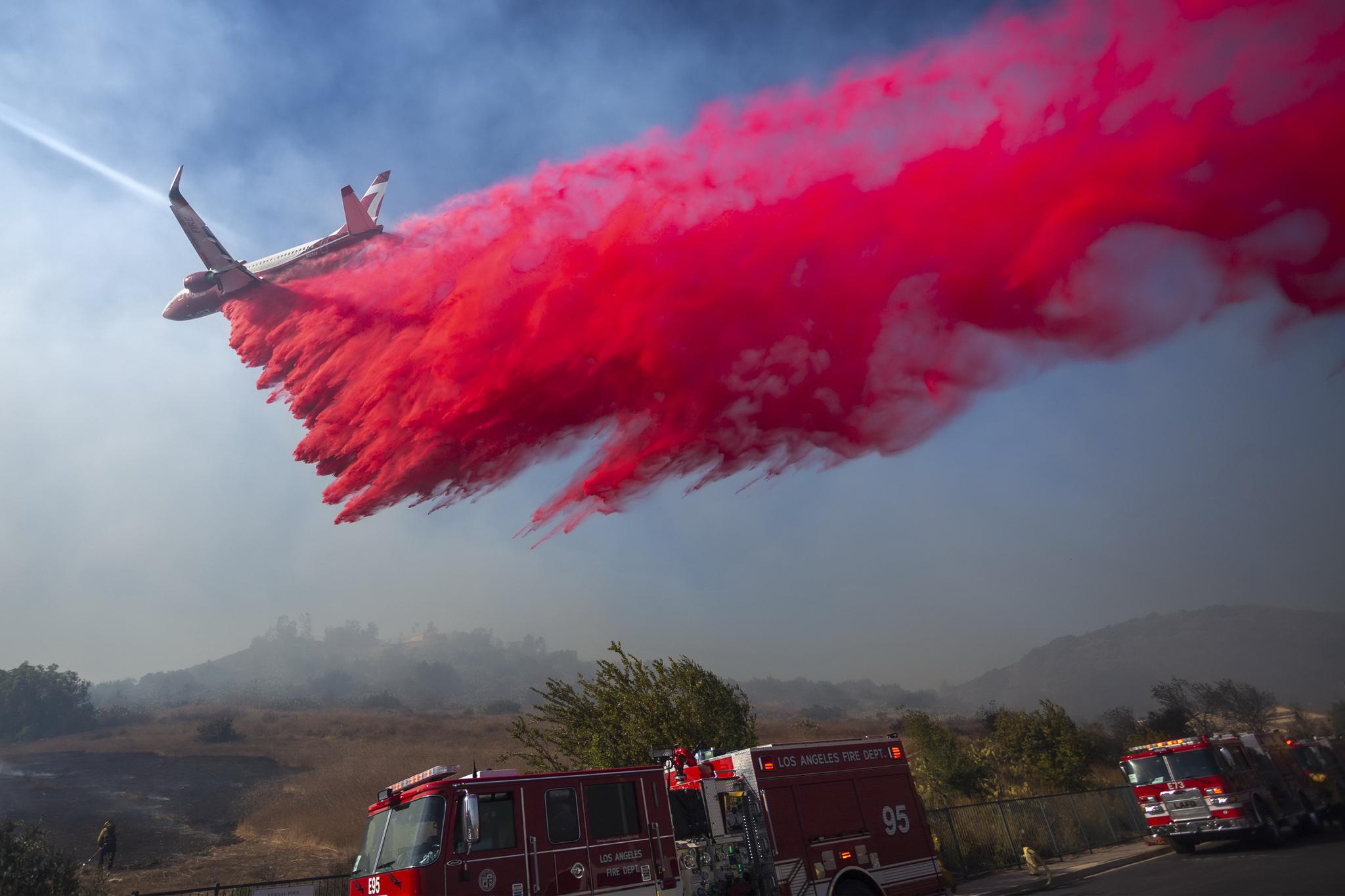 10월 30일 미국 캘리포니아 시미 계곡의 23번 프리웨이 상공에서 화재 진압용 비행기가 불이 옮겨붙을 것으로 예상되는 지역에 방화제를 살포하고 있다. [AFP=연합뉴스]