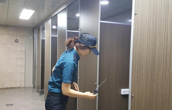 한 경찰관이 장비를 이용, 화장실에 몰래카메라가 설치됐는지 여부를 확인하고 있다. [중앙포토]