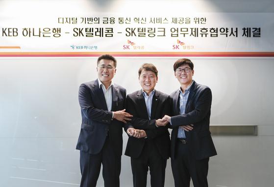 SK텔레콤과 KEB하나은행, SK텔링크는 1일 서울 을지로 SK텔레콤 본사에서 '디지털 기반의 금융?통신 혁신 서비스 제공을 위한 양해각서(MOU)'를 체결했다. 체결식엔 SK텔레콤 김성수 MNO사업부 영업본부장(오른쪽), KEB하나은행 염정호 미래금융사업본부장(가운데), SK텔링크 김선중 대표(왼쪽) 등이 참석했다. [사진 SK텔레콤]