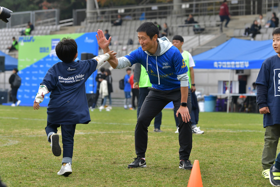 2일 서울월드컵보조구장에서 열린 한국컴패션 에이매치 행사에 참여한 이영표 홍보대사가 참가한 어린이와 하이파이브를 나누고 있다. [사진 올리브크리에이티브]