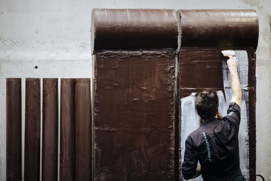 프랑스 초콜릿 제조사 패트릭로저 소속 예술가가 다크초콜릿과 화이트초콜릿으로 베를린장벽을 재현하고 있다. [AP=연합뉴스]