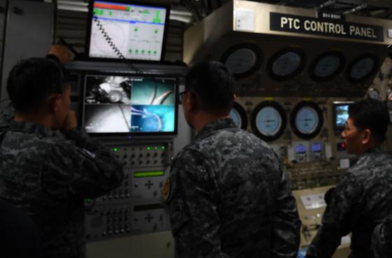 3일 오전 소방헬기 추락 독도 해역에서 해군 해난구조대원(SSU)들이 청해진함 인원이송장치 조정실에서 소방헬기 인양을 위한 포화 잠수작전을 지휘하고 있다. [사진 해양경찰청]