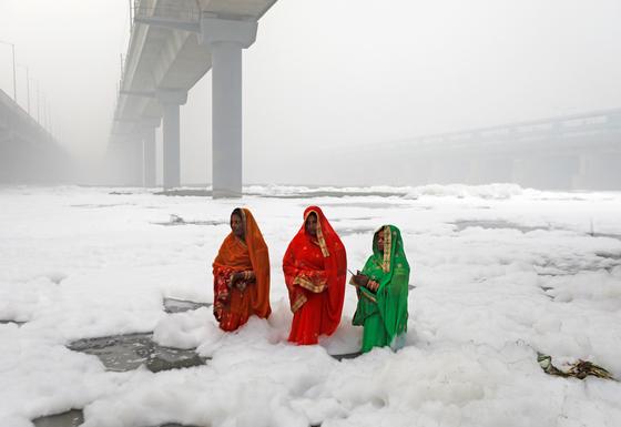 인도 뉴델리 여성들이 3일 오염된 강에서 힌두교 의식을 하고 있다. 오염 물질로 인해 눈이 내리지 않는 인도에 마치 눈이 내린듯 하얗다. [로이터=연합뉴스]