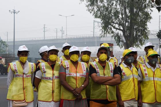 스모그가 자욱한 4일(현지시간) 뉴델리 시의 자원봉사자들이 정부가 시행한 차량 2부제 시행을 알리기 위해 거리에 서 있다. [AFP=연합뉴스]