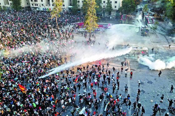 """지난 1일 칠레 산티아고의 이탈리아 광장에서 """"대통령 하야""""를 외치는 시위대를 향해 경찰이 물대포와 최루가스를 쏘고 있다. [연합뉴스]"""