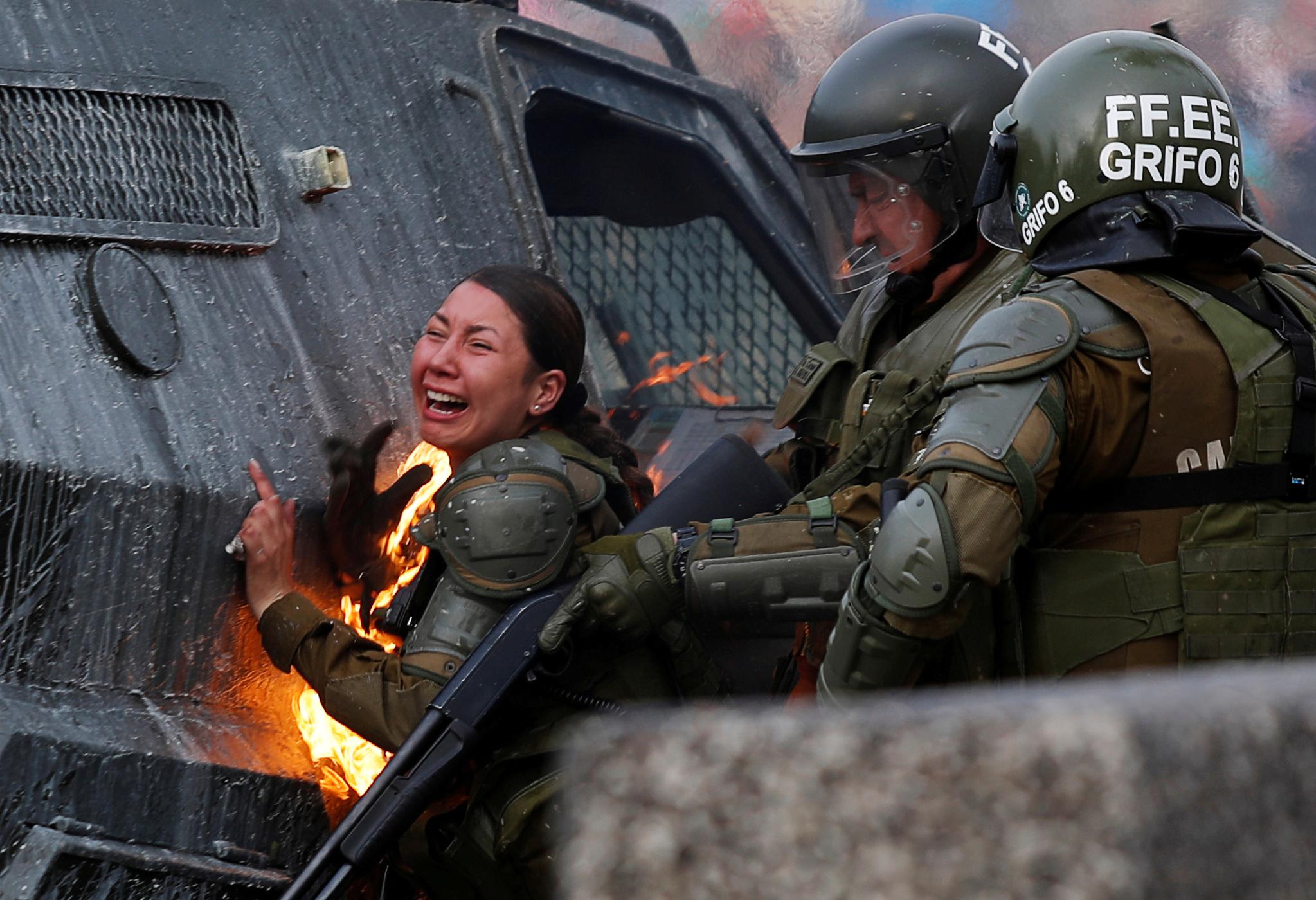 4일(현지시간) 칠레 산티아고에서 시위대가 던진 화염병에 불이 붙은 경찰이 고통을 호소하고 있다.[로이터=연합뉴스]