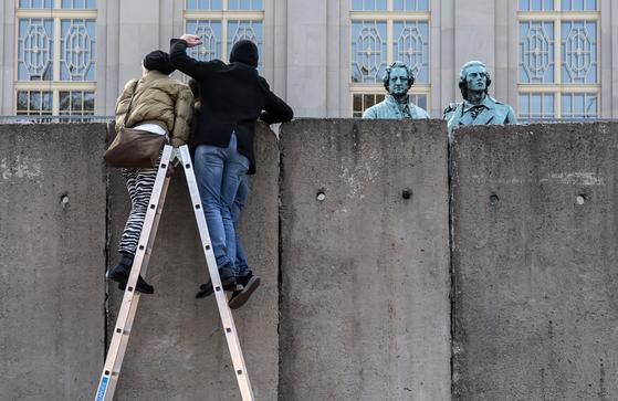 지난 달 30일(현지시간) 독일 바이마르에서 열린 베를린 장벽 붕괴 30주년 기념 공연에서 예술가들이 임시로 설치한 벽에 사다리를 설치하고 작가들의 동상이 있는 곳을 내다보고 있다. [AP=연합뉴스]