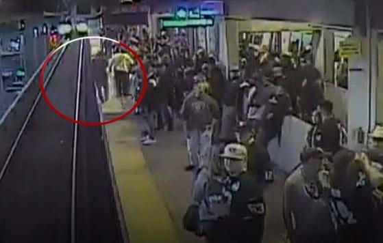 미국 오클랜드 콜로세움 역 승하차장에서 열차가 진입하기 몇 초 전 술에 취해 선로에 떨어진 한 남성(빨간 원)을 역 근무자가 구조하는 모습이 감시카메라에 포착, 공개됐다. [AP=뉴시스]