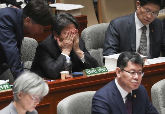 강기정 청와대 정무수석(가운데)이 6일 국회 예산결산특별위원회 전체회의에서 한 관계자의 말을 들으며 얼굴을 손으로 감싸고 있다.   임현동 기자