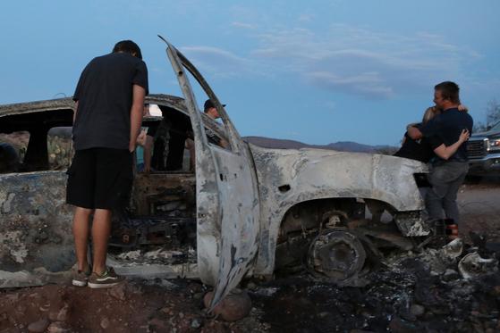 5일(현지시간) 멕시코 북부의 무차별 총격 사건이 벌어진 현장에서 피해자 가족들이 불에 탄 차량을 보고 오열하고 있다. [AFP=연합뉴스]