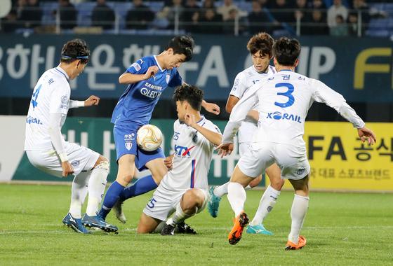 3부리그 대전 코레일(흰색 유니폼) 선수들이 1부 수원 삼성 선수를 에워싸 저지하고 있다. [연합뉴스]