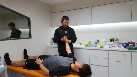 선수의 근육 상태를 점검하는 이 코치.
