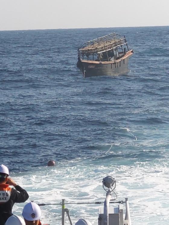 16명이 죽는 집단 살인 사건이 벌어졌다는 북한 목선. 해경이 8일 오후 2시께 동해상 북방한계선(NLL)에서 이 배를 북측에 인계하고 있다. [통일부 제공]