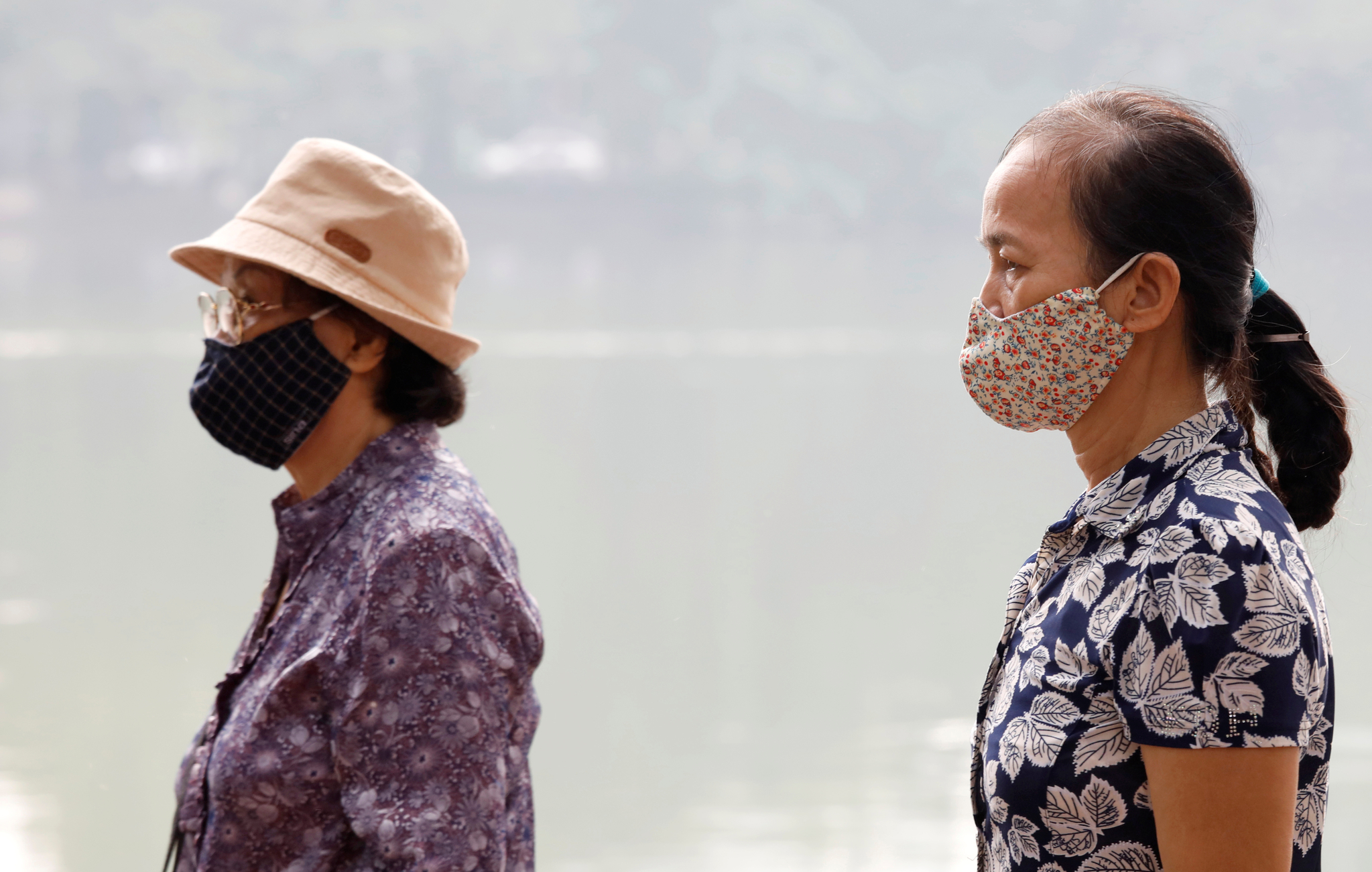 지난달 2일 스모그로 베트남 하노이 하늘이 뿌옇게 변한 가운데 베트남 여성들이 하노이 호안 키엠 호수 주변을 걷고 있다. [로이터=연합]