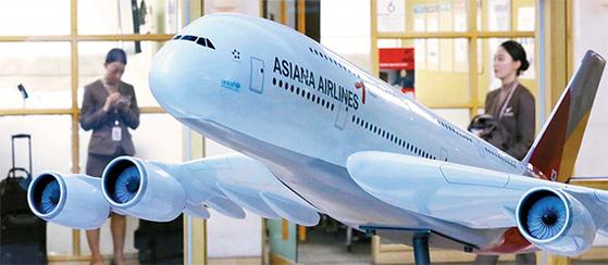 아시아나항공의 본입찰이 진행된 7일 오후 서울 강서구 오쇠동 아시아나항공 본사 로비에 전시된 모형 항공기 뒤로 승무원들이 지나가고 있다. [뉴시스]