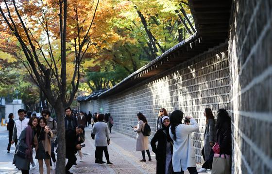 겨울의 시작을 알리는 절기 '입동(立冬)'인 8일 서울 중구 덕수궁에서 떨어진 낙엽 사이로 시민들이 걸어가고 있다. 주말인 9일은 전국이 대체로 맑겠다. [뉴스1]