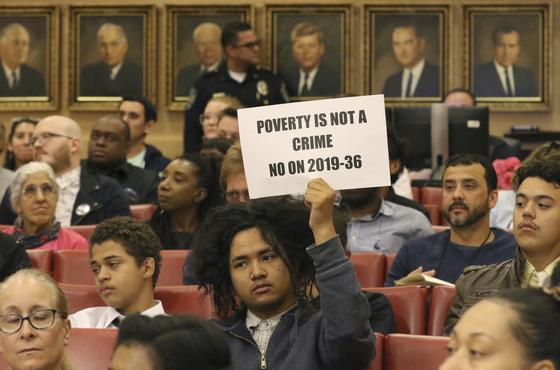 """지난 6일 라스베이거스시 시의회에서 한 시민이 """"가난은 죄가 아니다""""라는 문구를 들고 항의하고 있다. [AP=연합]"""
