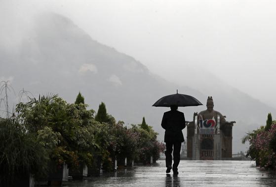 서울 종로구 광화문광장에서 한 시민이 우산을 쓰고 발걸음을 옮기고 있다. 기상청은 휴일인 10일 오후에 서해안을 시작으로 밤에는 전국에서 가을비가 내리겠다고 예보했다. [연합뉴스]