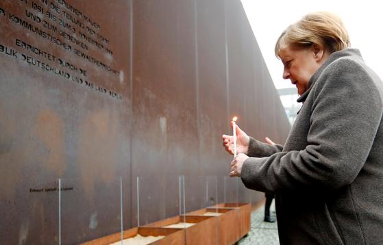 앙겔라 메르켈 독일 총리가 베를린 장벽 붕괴 30주년 기념식에 참석해 동독 정권 아래에서 희생된 이들을 추모하는 촛불을 들고 있다. [로이터=연합뉴스]