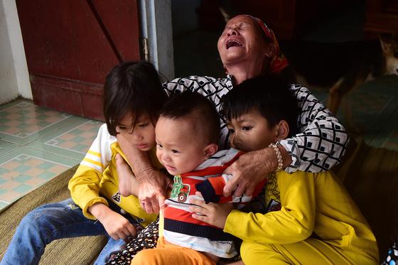 영국으로 돈을 벌기 위해 밀입국하려다 냉동컨테이너에서 희생된 한 남성의 어머니가 베트남에서 손주들을 껴안고 오열하고 있다. [EPA=연합뉴스]
