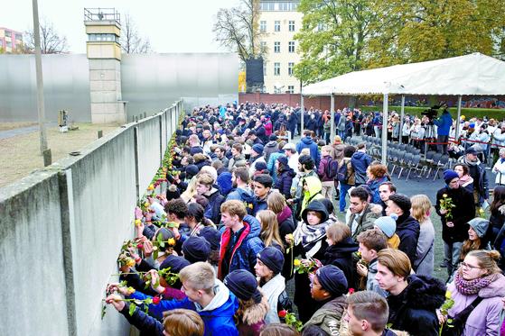베를린 장벽 붕괴 30주년을 맞은 9일(현지시간) 독일 베르나우어 스트라스에서 시민들이 분단의 상징이었던 장벽에 꽃을 꽂고 있다. [AP=연합뉴스]