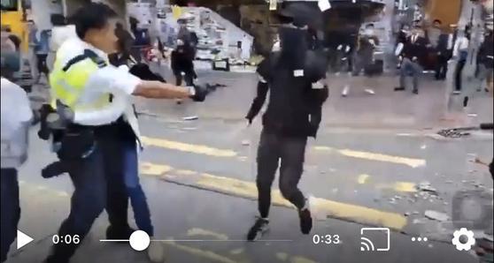 홍콩 경찰이11일 오전 시위대 체포를 만류하려던 복면 시위자를 향해 권총으로 실탄을 발사하고 있다. [트위터 캡처]