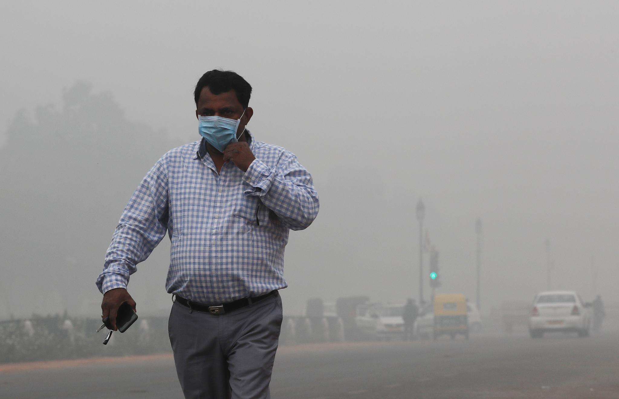 지난 3일 짙은 스모그가 낀 인도 뉴델리 거리를 마스크를 쓴 시민이 걷고 있다. [로이터=연합]
