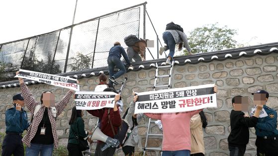 한국대학생진보연합 소속 대학생이 18일 오후 서울 중구 주한 미국대사관저에서 방위비분담금 협상 관련 기습 농성을 하기 위해 담벼락을 넘고 있다. [뉴시스]