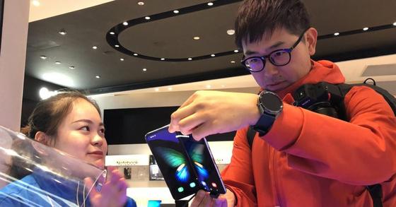 지난 8일 중국 상하이 번화가 난징둥루에 있는 삼성전자 플래그십 매장에서 고객이 갤럭시 폴드를 살펴보고 있다. [상하이=연합뉴스]
