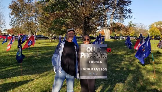 """7일 워싱턴 미 의회 하원 앞에서 케빈과 샤론이 """"대가 제공이 압력""""이라는 팻말을 들고 있다. 정효식 특파원"""