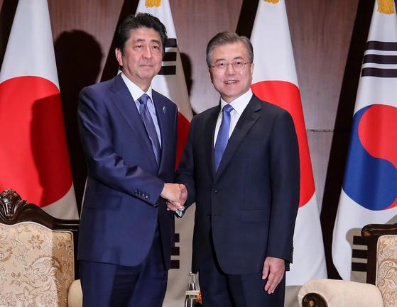 지난해 9월 유엔 총회 참석 중인 문재인 대통령과 아베 신조 일본 총리가 미국 뉴욕 파커 호텔에서 만나 악수하고 있다. [연합뉴스]