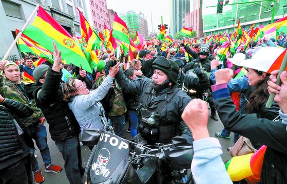 에보 모랄레스 볼리비아 대통령이 사임한 10일(현지시간) 시민들이 수도 라파즈 시내에서 경찰들과 기쁨을 나누고 있다. [EPA=연합뉴스]