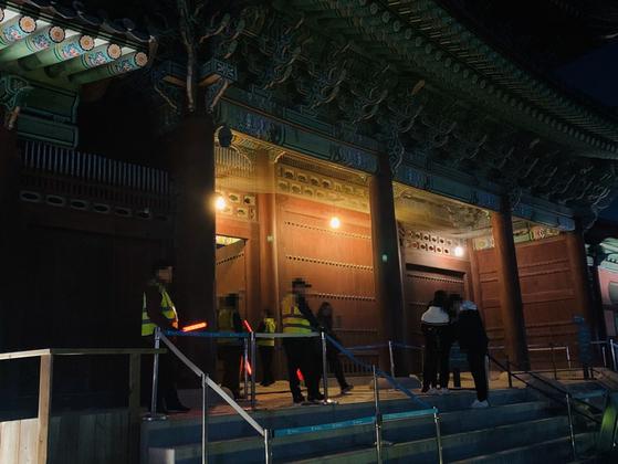 지난 6일 정부의 노인 일자리 사업으로 고용된 안내 요원(형광색 조끼)들이 야간 개장한 서울 시내 한 고궁에서 관람객의 입장권을 검사하고 있다. [허정원 기자]