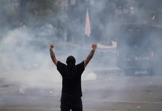 11일 칠레 산티아고에서 한 시민이 진압 경찰을 향해 저항의 몸짓을 보이고 있다. [EPA=연합뉴스]